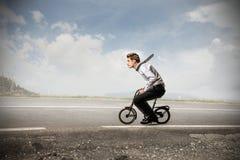Homme d'affaires montant un vélo photos stock