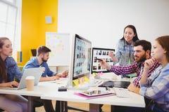 Homme d'affaires montrant l'écran d'ordinateur aux collègues image stock