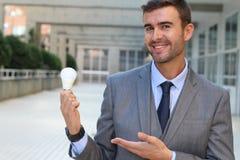 Homme d'affaires montrant l'ampoule dans l'immeuble de bureaux Photo libre de droits
