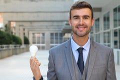 Homme d'affaires montrant l'ampoule dans l'immeuble de bureaux Photo stock