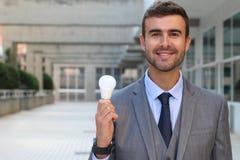 Homme d'affaires montrant l'ampoule dans l'immeuble de bureaux Image stock