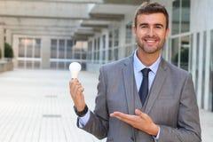 Homme d'affaires montrant l'ampoule dans l'immeuble de bureaux Images libres de droits