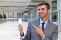 Homme d'affaires montrant l'ampoule dans l'immeuble de bureaux Photos libres de droits