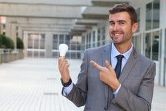 Homme d'affaires montrant l'ampoule dans l'immeuble de bureaux Image libre de droits