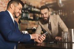 Homme d'affaires montrant l'information au téléphone au barman photos stock