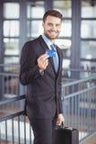 Homme d'affaires montrant la carte de crédit tout en se tenant dans le bureau image libre de droits