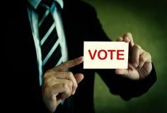 Homme d'affaires montrant la carte de vote Photos stock