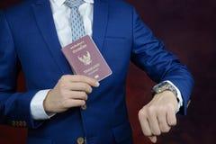 Homme d'affaires montrant le passeport, temps de contrôle sur la montre Images stock