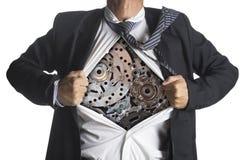 Homme d'affaires montrant un costume de super héros sous des machines Photographie stock libre de droits