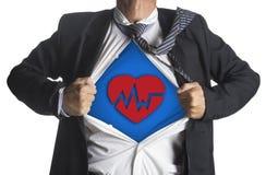 Homme d'affaires montrant un costume de super héros sous le battement de coeur Images libres de droits