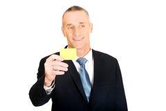 Homme d'affaires montrant une carte nominative jaune d'identité Images stock