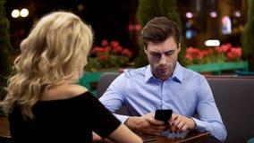 Homme d'affaires ne prêtant pas l'attention à son amie, adonnée à l'instrument, problème photo stock