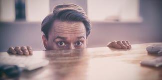 Homme d'affaires nerveux jetant un coup d'oeil au-dessus du bureau Photographie stock libre de droits