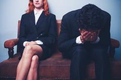 Homme d'affaires nerveux s'asseyant à côté de la femme d'affaires sûre Image libre de droits