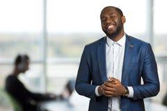 Homme d'affaires noir de sourire dans le bureau Photographie stock
