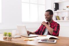 Homme d'affaires noir de sourire dans le bureau occasionnel, travail avec l'ordinateur portable Image stock