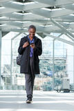 Homme d'affaires noir de sourire marchant avec le téléphone portable à l'aéroport Photo stock