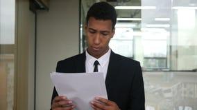 Homme d'affaires noir Reading Documents dans le bureau banque de vidéos