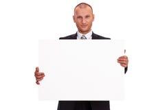 Homme d'affaires non rasé dans un costume foncé, tenant un grand signe, c blanc Photo stock