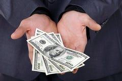 Homme d'affaires nous affichant une certaine somme d'argent Image stock