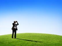 Homme d'affaires observant la nature avec un télescope Images stock