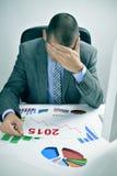 Homme d'affaires observant un diagramme avec une évolution à la baisse pendant 2015 Image libre de droits
