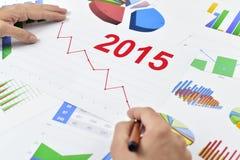 Homme d'affaires observant un diagramme avec une évolution à la baisse pendant 2015 Photos stock