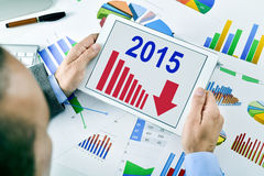 Homme d'affaires observant un diagramme avec une évolution à la baisse pendant 2015 Photo libre de droits