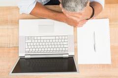 Homme d'affaires occasionnel épuisé se penchant sur le bureau en bois image stock