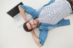 Homme d'affaires occasionnel décontracté se trouvant sur son ordinateur portable photos stock