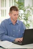 Homme d'affaires occasionnel dans le bureau tout en dactylographiant sur l'ordinateur portable Image stock