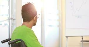 Homme d'affaires occasionnel dans le fauteuil roulant écoutant la présentation clips vidéos