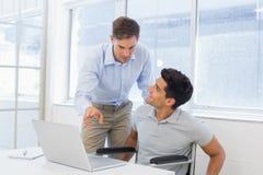 Homme d'affaires occasionnel dans le fauteuil roulant parlant avec le collègue à l'aide de l'ordinateur portable images libres de droits