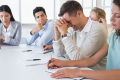 Homme d'affaires occasionnel essayant de ne pas rire au cours de la réunion images stock