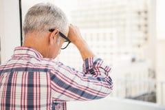 Homme d'affaires occasionnel préoccupé se penchant contre la fenêtre photo libre de droits