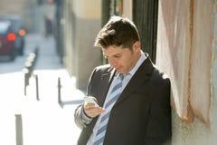 Homme d'affaires occupé dans le costume et lien utilisant le téléphone portable envoyant l'Internet de consultation de message photo libre de droits