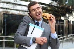 Homme d'affaires occupé marchant, appelle et prenant le déjeuner simultanément Photos stock