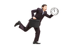 Homme d'affaires occupé exécutant avec l'horloge murale et la serviette Image libre de droits