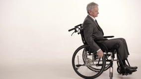 Homme d'affaires paraplégique sur un fauteuil roulant Projectile de studio banque de vidéos