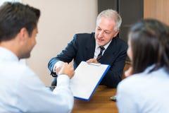 Homme d'affaires parlant à un couple Image libre de droits