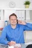 Homme d'affaires parlant au téléphone à son bureau photo stock