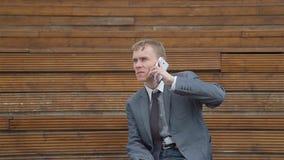 Homme d'affaires parlant au téléphone en dehors du bureau banque de vidéos