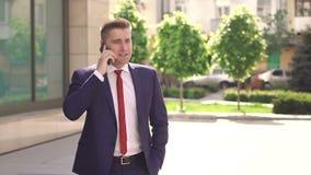 Homme d'affaires parlant au téléphone en parc de ville banque de vidéos