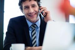Homme d'affaires parlant au téléphone et à l'aide de son ordinateur portable Photographie stock libre de droits