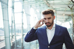 Homme d'affaires parlant au téléphone portable à la gare ferroviaire Images libres de droits