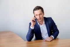 Homme d'affaires parlant au téléphone portable dans le bureau photo libre de droits