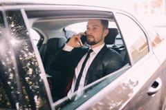 Homme d'affaires parlant au téléphone portable et regardant en dehors de la fenêtre tout en se reposant sur le siège arrière de l photos libres de droits