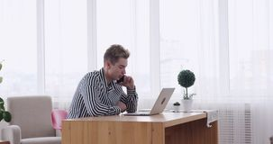 Homme d'affaires parlant au téléphone portable tandis qu'utilisant l'ordinateur portable au bureau banque de vidéos