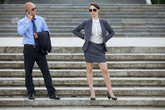 Homme d'affaires parlant au téléphone tandis que femme d'affaires se tenant sur des étapes Images stock