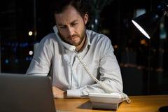 Homme d'affaires parlant au téléphone tout en travaillant dans le bureau Image stock